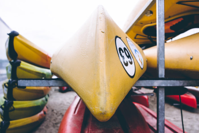 Closeup Photo of Yellow Kayak on Gray Metal Rack